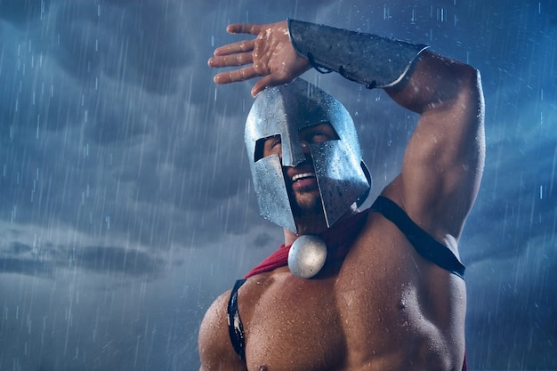 Portrait of spartan warrior getting wet in rain and raising hand. close up of man in red cloak and helmet with water drops posing in dark cloudy atmosphere outdoors. ancient sparta, warrior concept.