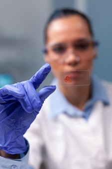 Portrait of specialist doctor analyzing blood sample test working at genetic experiment