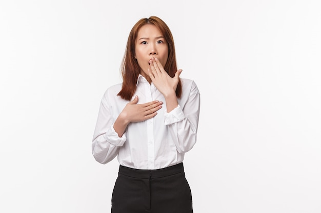 Portrait of speechless shocked asian office lady, woman gasping cover mouth and staring disbelief camera as hear something concerning, gossiping with coworkers, stand