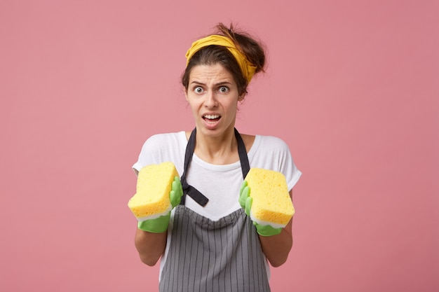 Ritratto di giovane donna viziata che indossa la fascia, il grembiule e i guanti di gomma verde sentendosi frustrata mentre deve fare tutto da sola, tenendo le spugne tra le mani, guardando confusa