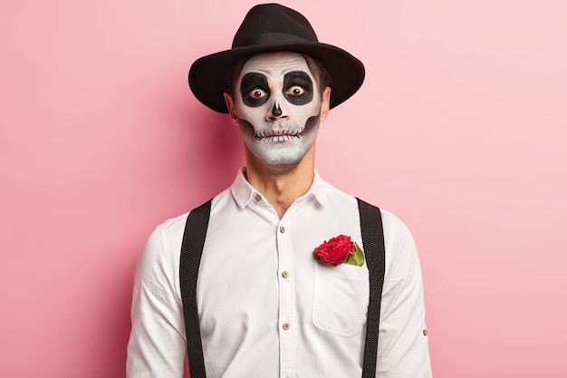 Portrait of spooky handsome guy made makeup for halloween event, has image of vampire or ghost, red rose flower in pocket of white shirt, wears black hat, has scary look