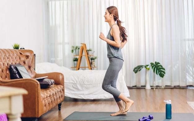 운동복을 입은 세로 스포츠 미인 몸매 슬림 여성은 긴장을 풀고 달리기를 하고 피트니스 운동을 합니다.