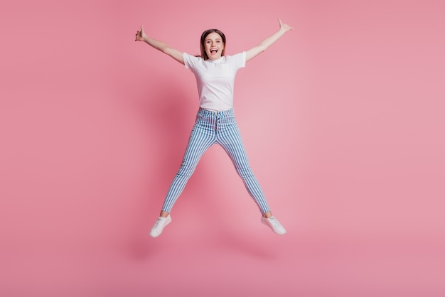 Portrait of sportive childish funky girl jumping in the air wear casual denim outfit on pink wall
