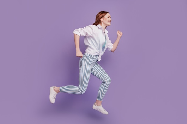 Portrait of sportive energetic lady jump run copyspace on purple background