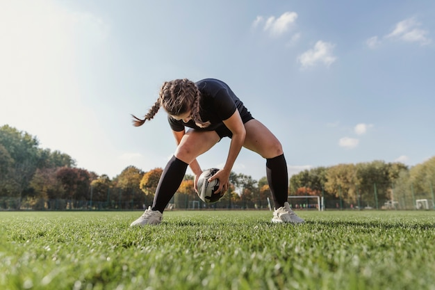 Portrait of sportive girl playing with a rugby ball