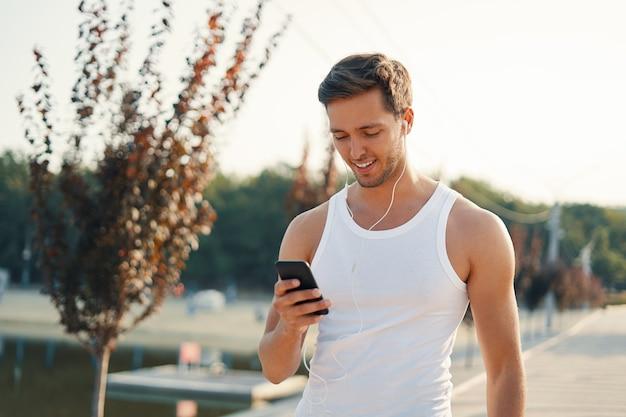 Портрет спортивный мужчина с мобильным телефоном
