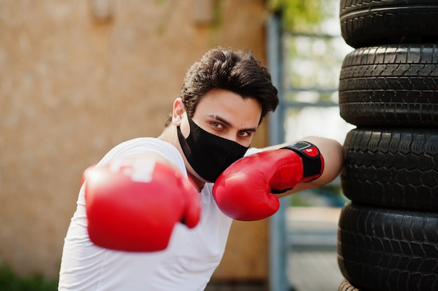 Portrait sports arabian boxer man in black medical face mask boxing outdoor during coronavirus quarantine.