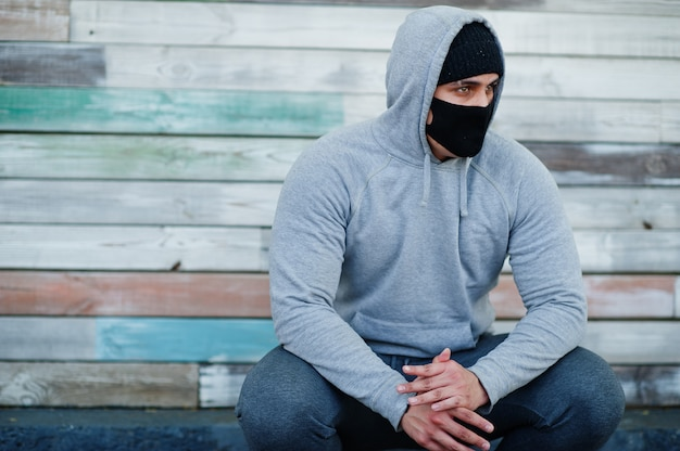 Portrait sports arabian man in black medical face mask and hoodie during coronavirus quarantine.