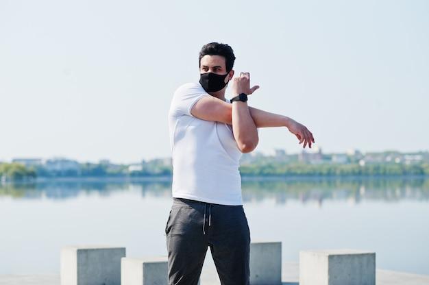 肖像画は、コロナウイルスの検疫中に湖に対して朝のワークアウト演習を行う黒い医療フェイスマスクのアラビア人をスポーツします。