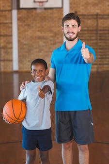 Portrait of sports teacher and schoolboy showing thumbs up