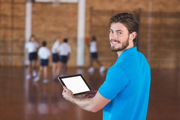 Portrait of sports teacher using digital tablet