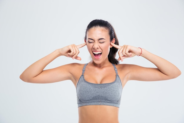 Portrait of a sports woman covering her ears with fingers and screaming isolated on a white wall