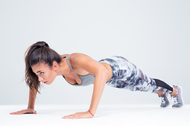 Portrait of a sports woman doing push ups isolated on a white wall