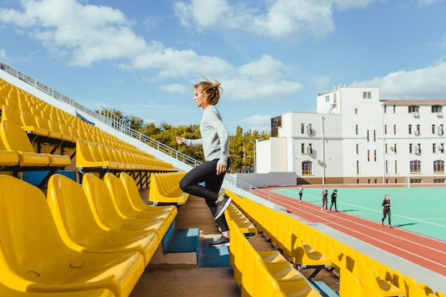 Portrait of a sports woman running at stadium