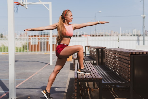 Portrait of a sports, young girl in sportswear and glasses, doing stretching on the playground