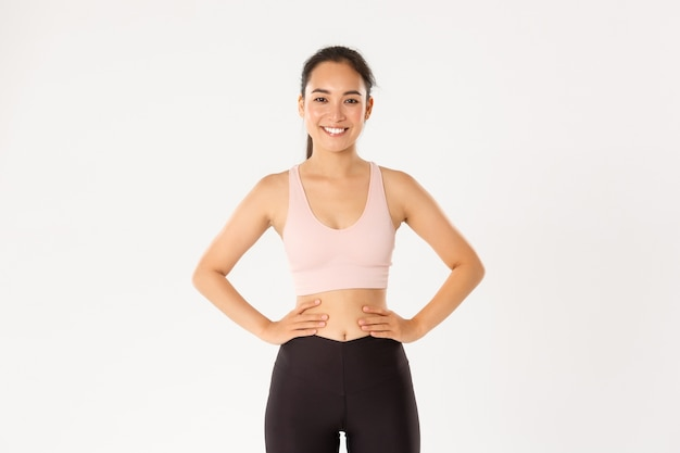 Portrait of sportswoman in activewear standing confident   female athlete, fitness coach looking upbeat, starting training session.
