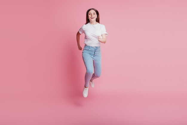 Portrait of sporty active crazy girl jumping in the air wear casual denim outfit on pink wall