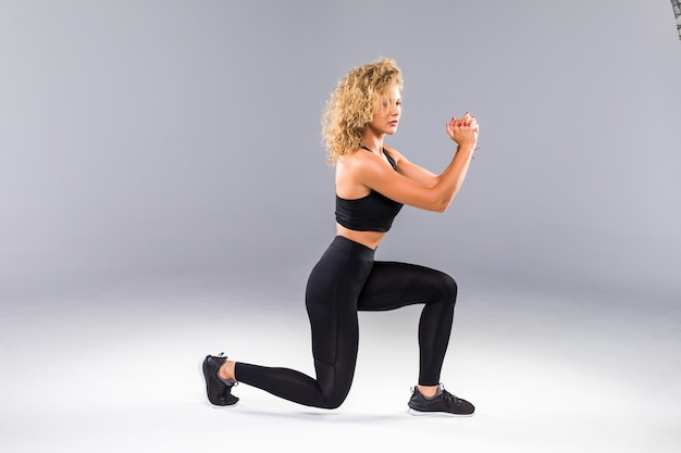Portrait of sporty athletic woman in sneakers and tracksuit squatting doing sit-ups in gym isolated over gray wall