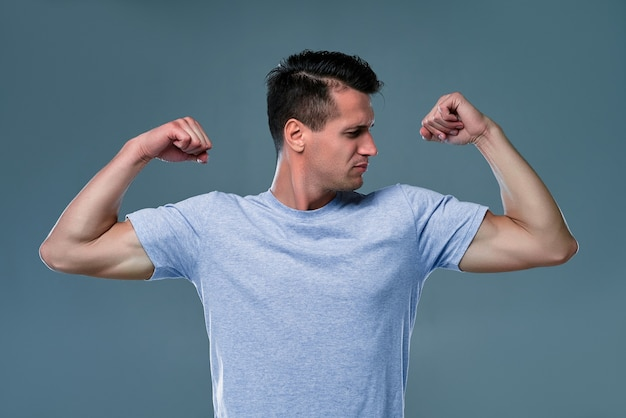 Portrait of sporty, attractive, powerful, virile, harsh, sexy guy in t-shirt with raised arms, having relief muscles on his hands, isolated on gray background