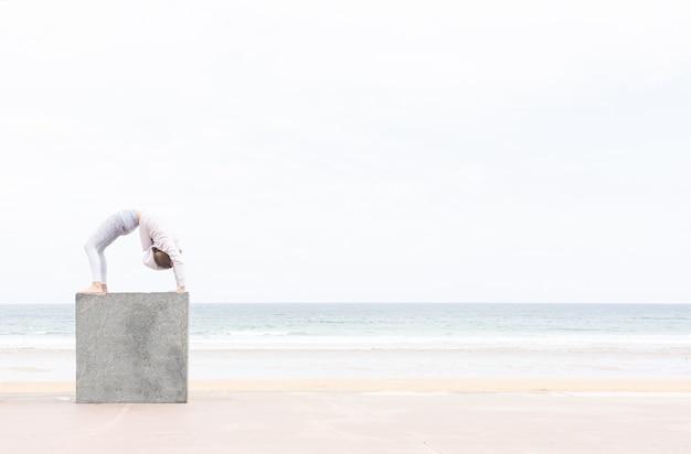 Portrait of sporty beautiful blond young woman in sportswear working out in the beach, doing deep back bend, bridge pose, urdhva dhanurasana (upward bow), chakrasana (wheel) posture on a cube