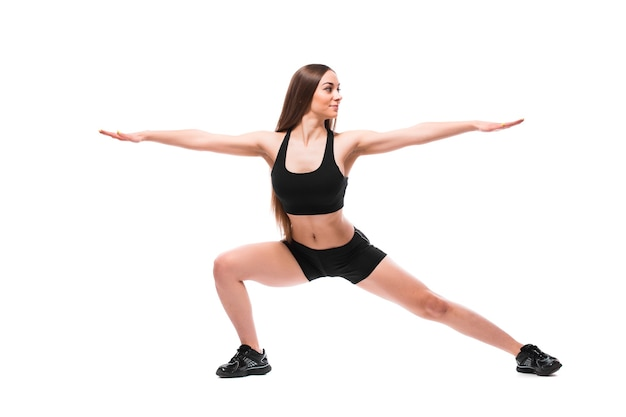 Portrait of sporty fit woman in sportswear working out, doing exercises isolated on white background