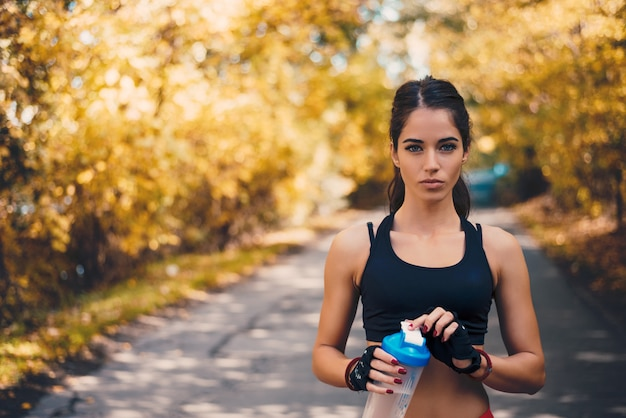 Portrait of sporty girl with sports gloves holding water bottle.