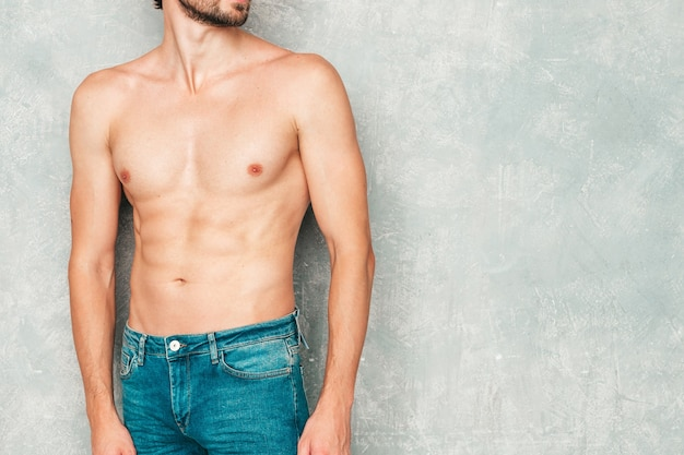 Portrait of sporty handsome strong man. healthy athletic fitness model posing near gray wall in jeans.