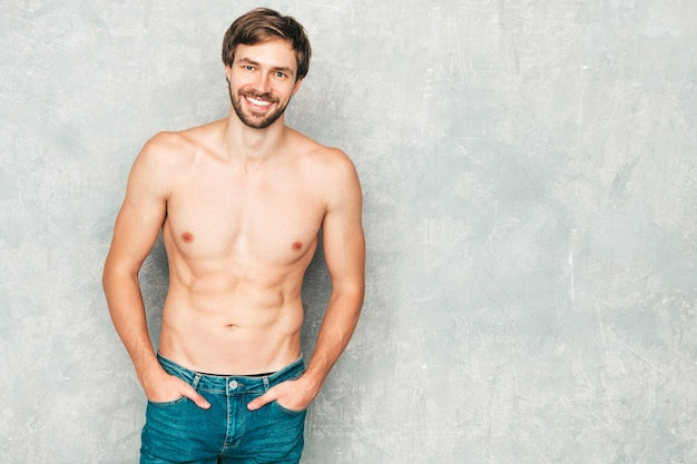 Portrait of sporty handsome strong man. healthy smiling athletic fitness model posing near gray wall in jeans.