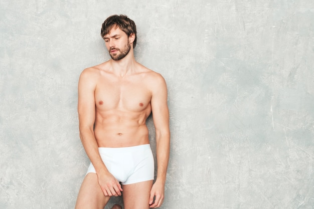 Portrait of sporty handsome strong man. healthy smiling athletic fitness model posing near gray wall in white underwear.