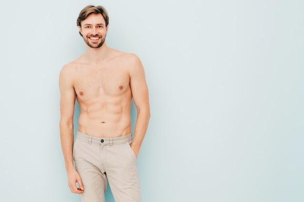 Ritratto di uomo forte bello sportivo. modello di fitness atletico sorridente sano in posa vicino alla parete blu chiaro