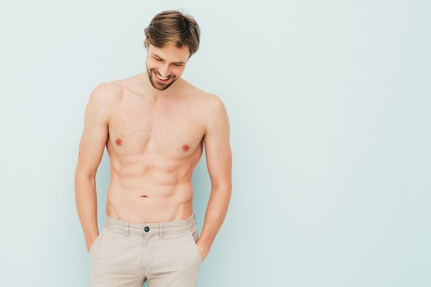 Portrait of sporty handsome strong man. healthy smiling athletic fitness model posing near light blue wall