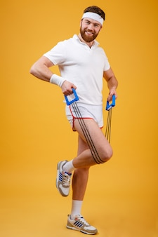 Portrait of a sporty man exercising with rubber expander