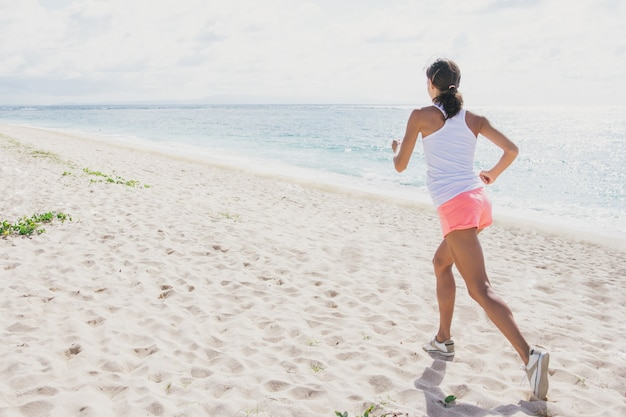 Portrait of sporty woman jogging at the beach