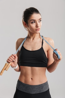 Portrait of sporty woman looking aside and holding jumping rope on her neck, isolated over gray wall