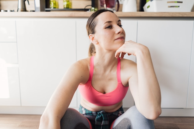 Portrait sporty woman resting after workout at home