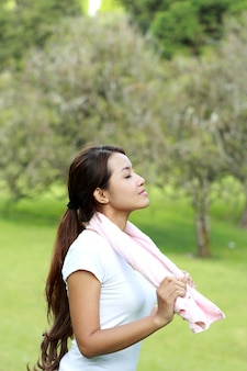 Portrait of sporty woman take a deep breath at the park with fresh air