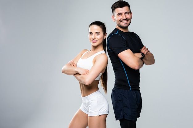 Portrait of a sporty young couple with arms crossed over white background