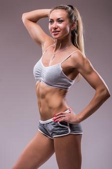 Ritratto di giovane donna sportiva con corpo muscoloso, in posa su uno sfondo grigio