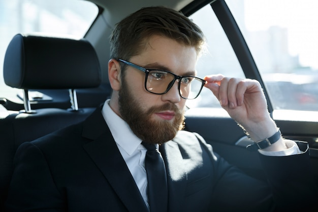 Portrait of a srious young man wearing suit and eyeglasses