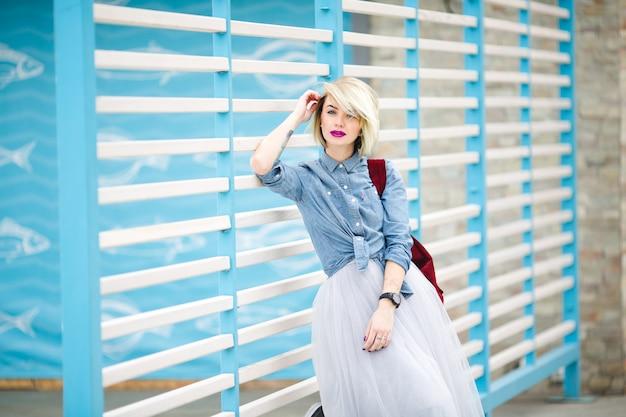 Ritratto di una donna sognante in piedi con capelli biondi corti, labbra rosa brillante e trucco nudo appoggiato alla recinzione a strisce bianche e blu