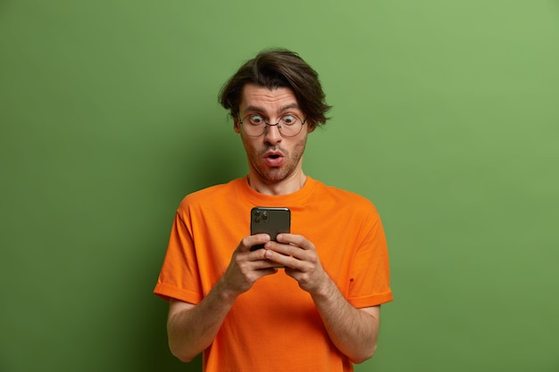 Portrait of startled impressed man stares at smartphone display, cant believe own eyes, gets shocking message, opens mouth and holds breath, wears orange t shirt, poses against green wall