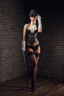 Portrait of steampunk girl in hat with glasses and cane in leather vest and stockings.