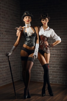 Portrait of steampunk girls in hat with glasses and cane in leather vest and stockings.