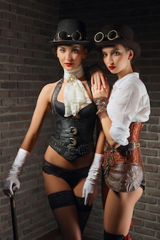 Portrait of steampunk girls in hat with goggles and cane in leather vest and stockings.
