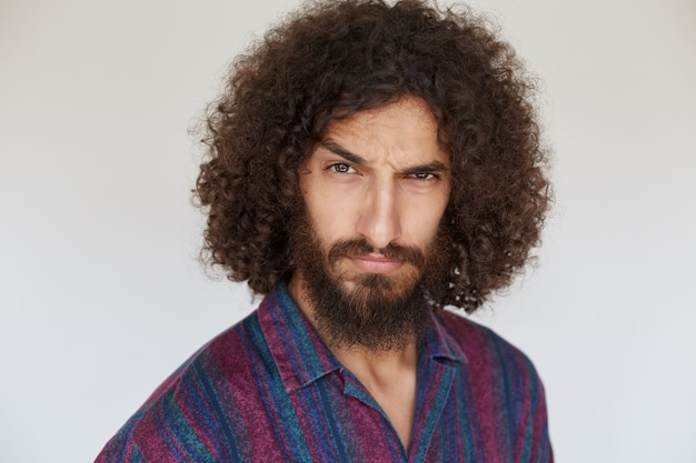 Portrait of stern brunette bearded guy with dark curly hair raising eyebrow and looking severely, keeping lips folded in casual shirt