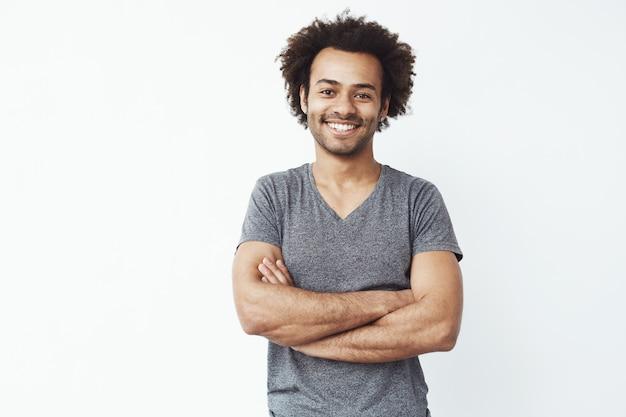 Ritratto dello studente maschio africano forte e bello che sorride con le armi attraversate sopra la parete bianca. presto sarà proprietario o venditore di startup.