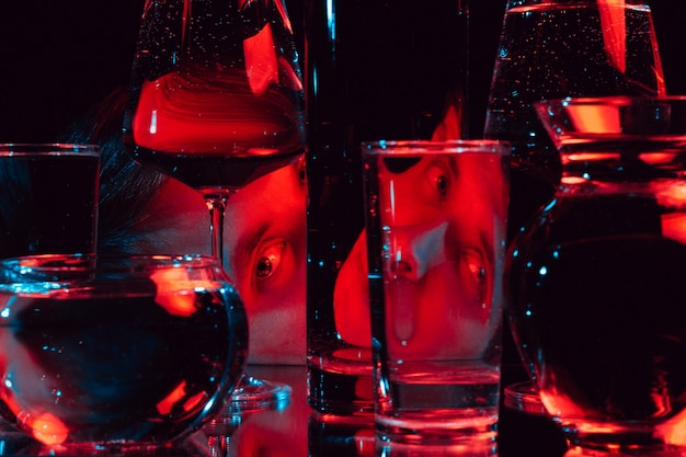 Portrait of a strange man looking through glass glasses of water with reflections and distortions with red blue neon light