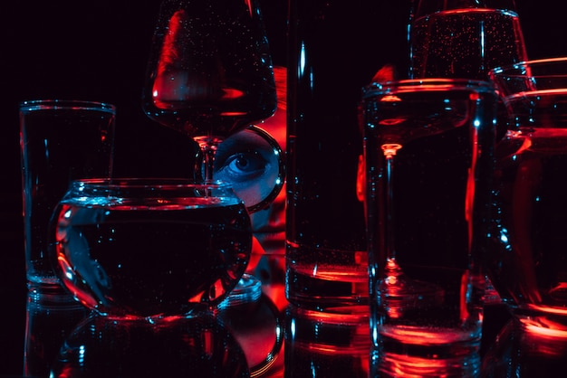Portrait of a strange man looking through a magnifying glass and glasses with water with red lights