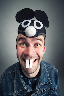 Portrait of strange young man with mouse ears and teeth