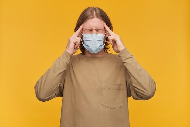 Ritratto di maschio adulto stressato con barba e capelli biondi. indossare un maglione beige e una maschera protettiva medica. massaggiare le tempie, soffrire di mal di testa. stare isolato su una parete gialla